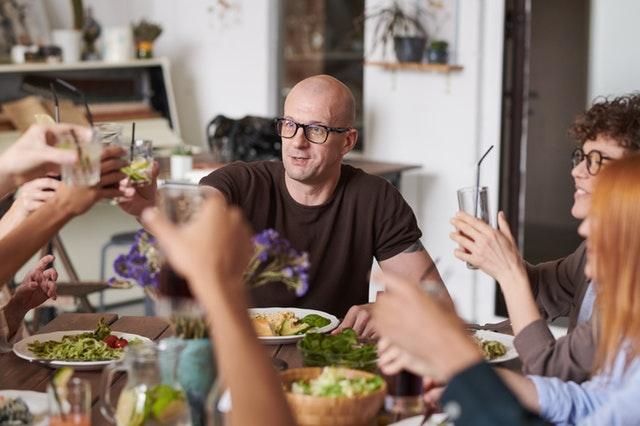 Rodina sedící kolem stolu s přípitkem v rukou
